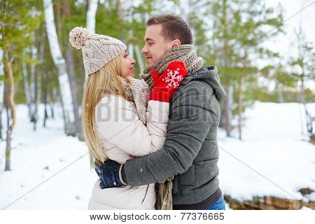 Young amorous couple embracing in winter outside
