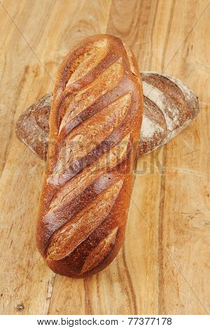 different rye and white flour french bread loaf with on light wooden table background