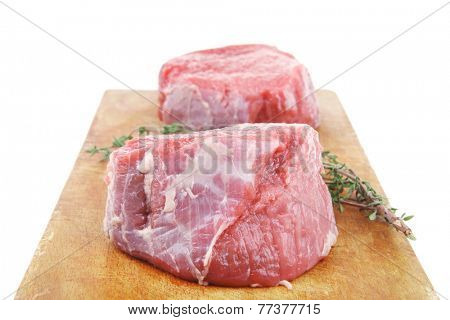 raw red meat : two fresh beef fillet chops with small thyme twig on wooden plate . isolated over white background