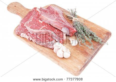 fresh raw beef meat fillet flesh with peppercorn and thyme ready to grill on wood figured old style board isolated over white background