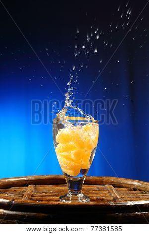 orange splashing into glass of water