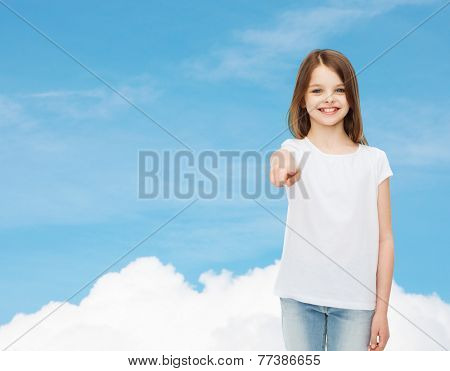 advertising, dream, childhood, gesture and people - smiling little girl in white t-shirt pointing finger on you over blue sky background