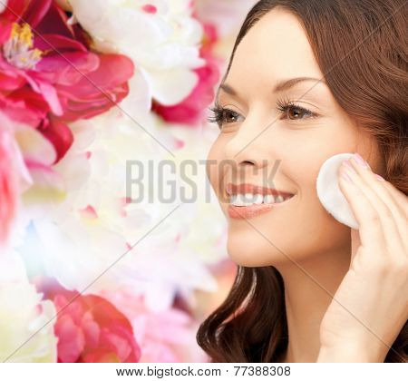 beauty, people and health concept - beautiful smiling woman cleaning face skin with cotton pad over pink floral background