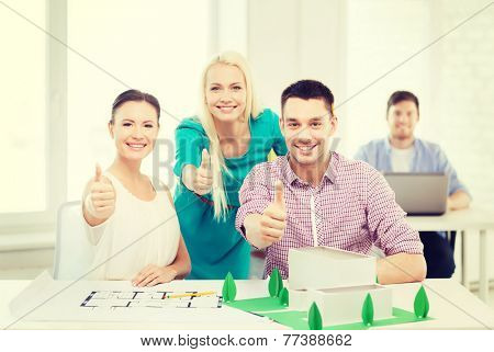 startup, education, architecture and office concept - smiling architects with house model and blueprint in office showing thumbs up