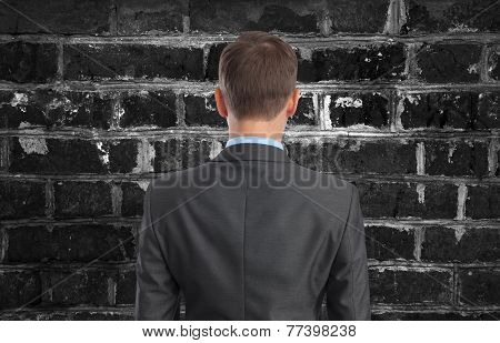 Businessman Looking At Brick Wall