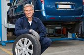 picture of mature adult  - Portrait Of Happy Mature Mechanic At Repair Service Station Holding A Tyre - JPG
