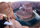 foto of bend  - photographer taking a picture of Horse Shoe Bend in Arizona belly crawling to the edge of the cliff - JPG