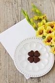 stock photo of gladiolus  - bouquet of yellow gladioluses chocolate hearts and a blank sheet of paper for inscription on the wooden background - JPG
