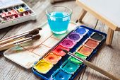 image of arts crafts  - Set of watercolor paints art brushes glass of water and easel with painting on old wooden table - JPG