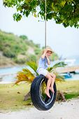 pic of tire swing  - Adorable little girl having fun on tire swing on summer day - JPG