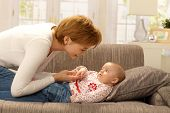 pic of caress  - Happy young mother caressing baby girl on sofa - JPG