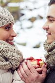 stock photo of amor  - Young amorous couple with small present looking at one another outdoors - JPG