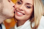 foto of sweetheart  - Amorous man kissing his sweetheart on cheek - JPG
