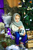 stock photo of knitted cap  - the girl in lilac jeans in a knitted cap and with a knitted scarf sits on a sledge near a Christmas fir-tree with a toy and it is snowing ** Note: Soft Focus at 100%, best at smaller sizes - JPG