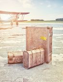 stock photo of old suitcase  - Vintage suitcases and retro airplane on runway - JPG