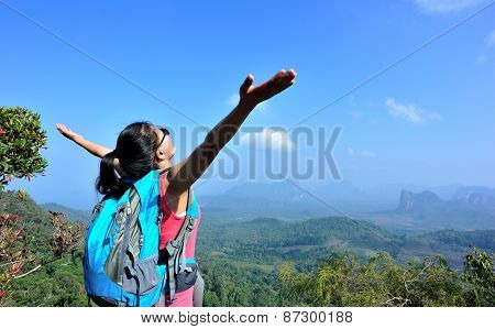 cheering young  woman hiker open arms at mountain peak