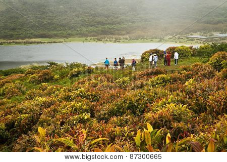 Group of unidentified tourists hiking along El Junco lagoon, San Cristobal Island, Galapagos