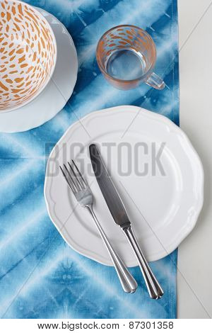 Empty plate on tabletop with tablecloth close up