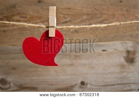 Red Fabric Heart Hanging On The Clothesline . On Wooden Background