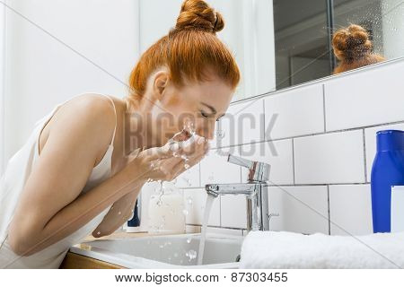 Woman Washing Her Face While Looking At The Camera