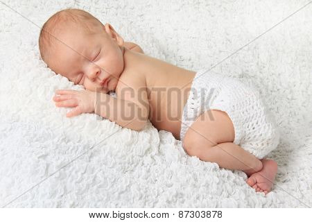 Sleeping Newborn baby boy wearing a knitted diaper cover.