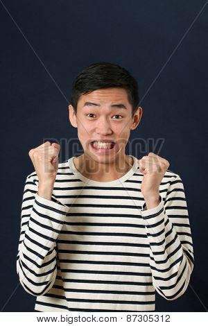Displeased young Asian man shaking two fists and looking at camera