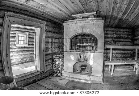 Interior Of Traditional Russian Wooden Bath With Brick Oven. Black And White Photo