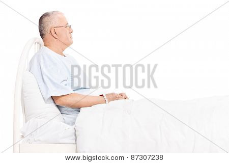 Studio shot of a senior patient in a hospital gown, lying in a bed and looking around isolated on white background
