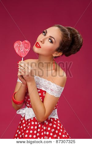 Happy Woman Holding red Lollipop Shape of Heart. Pin-up retro style.