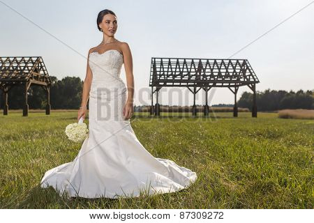 A modern bride poses outdoors with available light