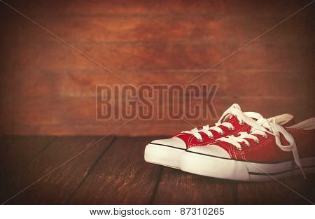 Red Gumshoes On Wooden Table