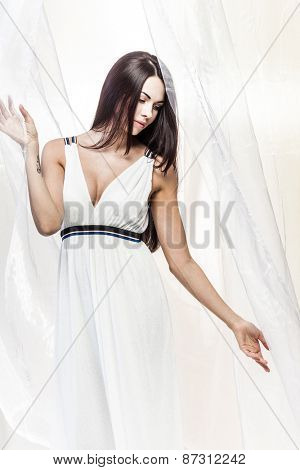 Fresh breeze is waving a piece of white silk fabric behind a beautiful young girl