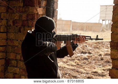 Man in mask with gun. Terrorism concept.