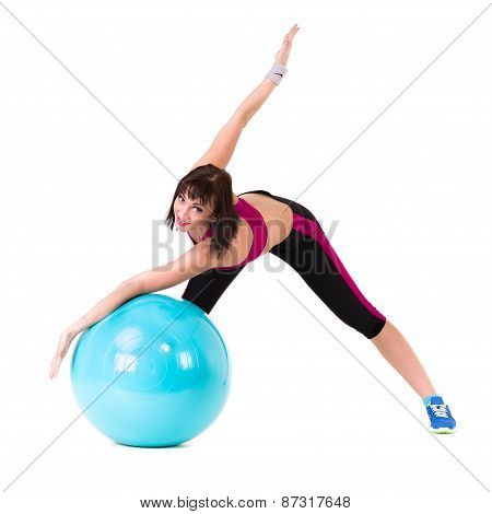 Young smiling woman makes exercise with fitball