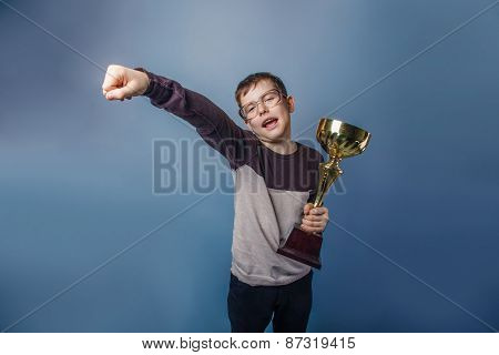 European-looking boy of ten years in glasses holding  a cup in h