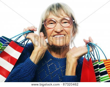 Happy senior woman with shopping bags isolated on white