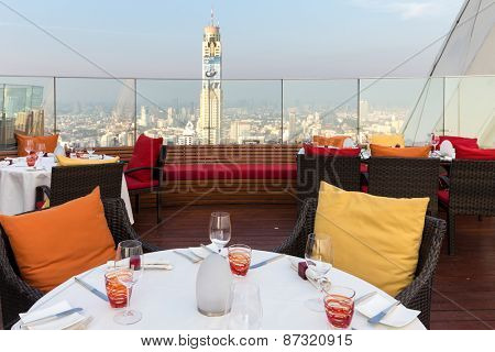 BANGKOK, THAILAND, JANUARY 14, 2015: Restaurant table with view on the Baiyoke tower and the cityscape at the Red Sky Rooftop of the Centara hotel in Bangkok, Thailand.