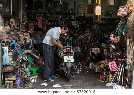 BANGKOK, THAILAND, JANUARY 15, 2015: A man is repairing a motorbike inside his modest garage shop in the Chinatown district of Bangkok, Thailand.