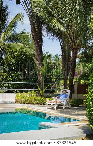 Elderly Tourist Resting By The Pool