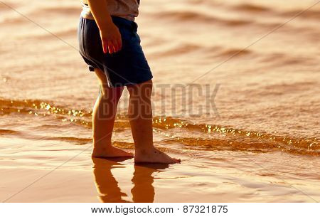 Child Standing Barefoot In The Water