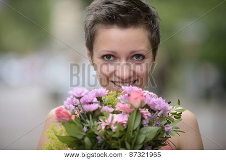 Happy woman holding floral arrangement in spring