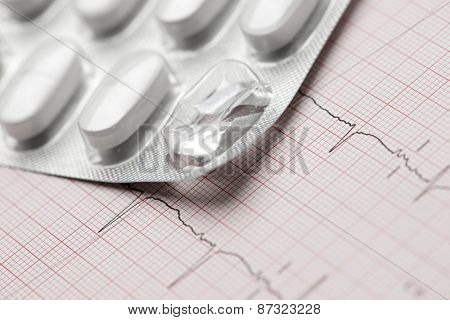 Forefront of a white medicine pills in blister pack and electrocardiogram.