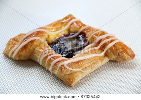 Danish pastry with blueberries jam on white.