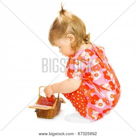Small baby in red dress with toy basket isolated