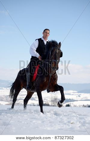 young man riding horse outdoor in winter