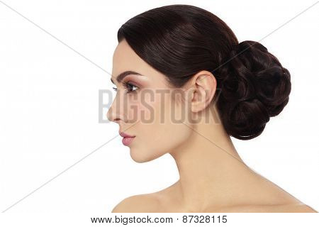 Profile portrait of young beautiful woman with stylish hair bun over white background, copy space
