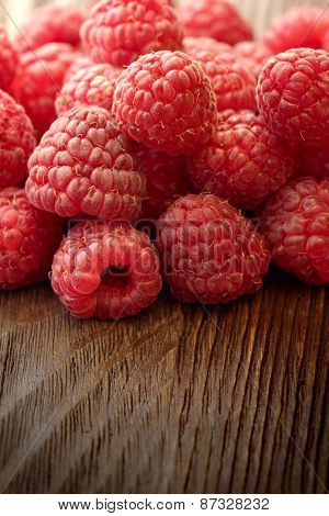 raspberries scattered on the wooden table