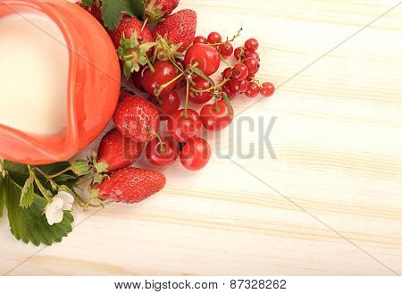 ripe juicy berries and jug on the table (focus on berry)