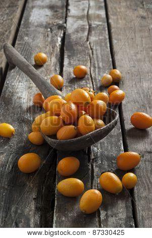 kumqats on a rustic wooden spoon