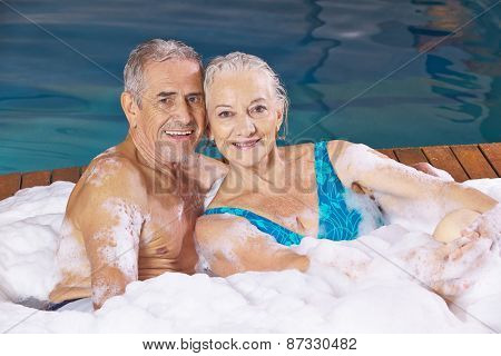 Happy senior couple taking foam bubble bath in a hotel whirlpool